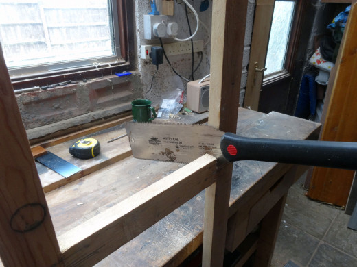 Using a Japanese saw to carefully remove the old middle rail.