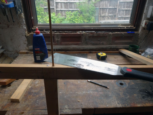 After gluing the dowels in place, cutting the dowel flush with the wood with a Japanese saw.