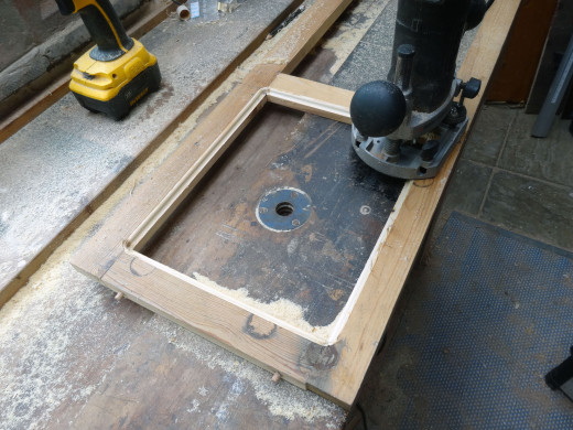 The decorative mouldings being routed on the reverse side to the glass recess; this router bit is self-guiding, so no clamp guide needed.