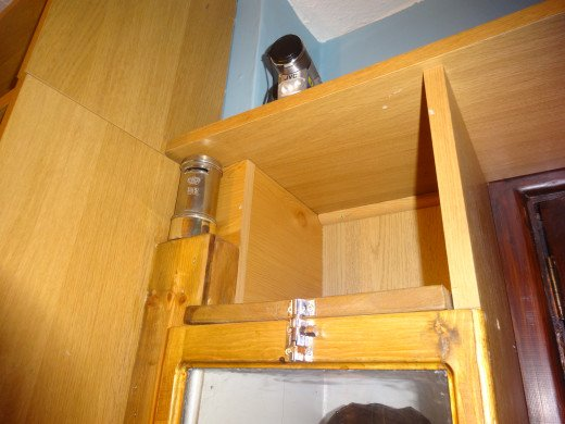 The bolt fitted to the top to secure the front panel in place, and above (on the left) the nook created, during the conversion from shelving to display cabinet, and left as a design feature for storing and displaying my son's silver plated money box.
