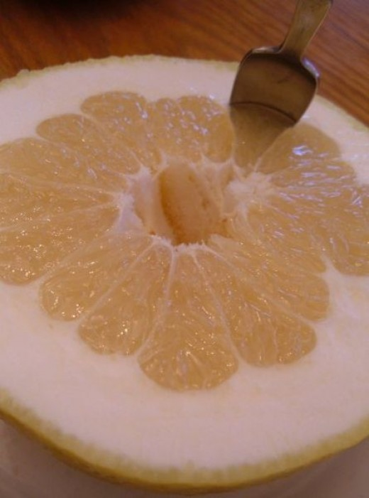 A grapefruit cut in half, ready to be eaten. This image is in the public domain.