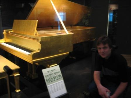 Me in front of Elvis' beautiful gold piano. I wanted to play it so badly!