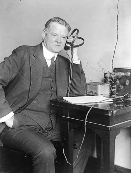 "Secretary of Commerce Hoover ""listening in"" on his radio set circa 1922."