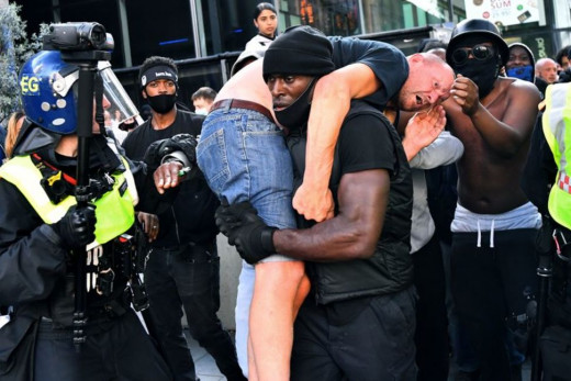 Courtesy of REUTERS/Dylan Martinez. Patrick Hutchinson, carrying a wounded far rightist to safety.