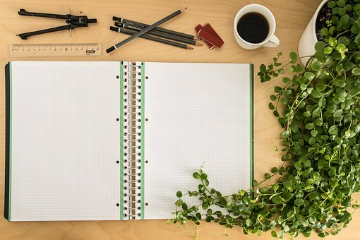 Notebook, coffee and other onjects on a desk to signify 3 vital devices to catapult your affiliate commissions