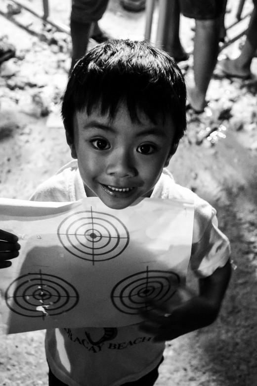 Little boy receiving a dart game toy