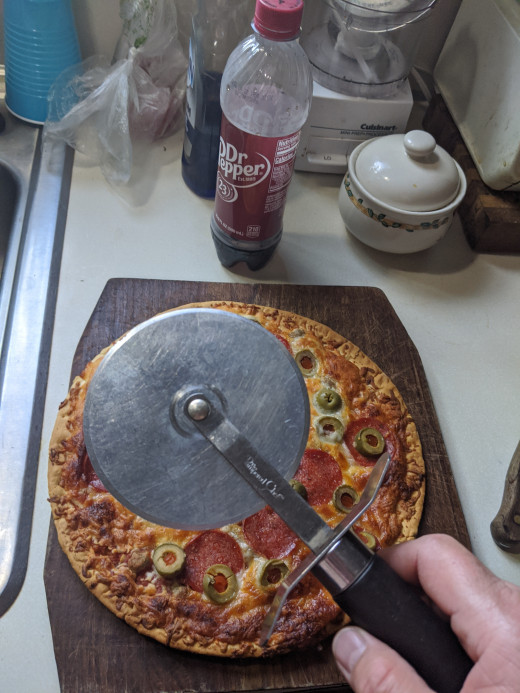 This is a pizza cutter. I will use it to illustrate the use of fractions. A fraction is a math term and means that I cut my whole piece into smaller pieces equally. You write the pizza cutter as '/'.