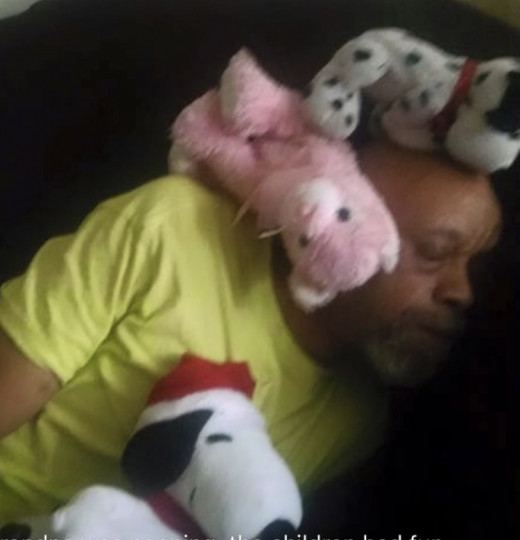 Grandchildren cover their Grampy with stuffed animals.