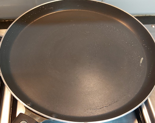 Heat tawa or pan on high flame. Smear some drops of oil and wipe off using cloth.