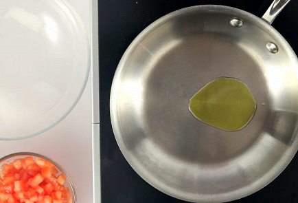 Heat a frying pan, pour in a little olive oil and pour in the tomatoes and garlic.