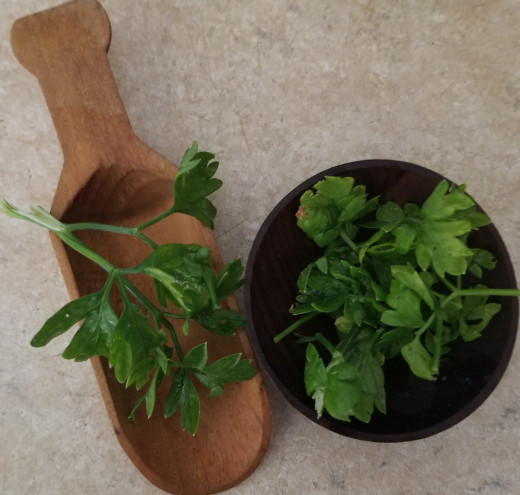 Parsley in small wooden bowl and spoon, ready to add to a plate of food as a garnish.