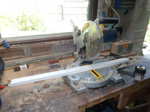 Cutting scrap wood to size for a kickboard for the base shelf.