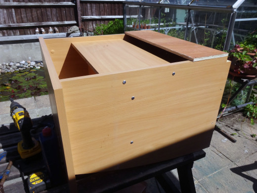 Using recycled veneered chipboard as a half height back stop for the base shelf; leaving a gap for cable management.