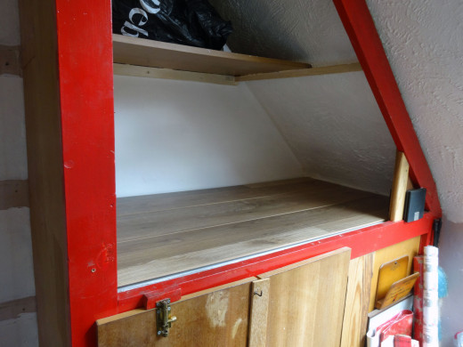 Laminate flooring laid inside the cupboard, using spare flooring leftover from repairs made to the office alcove.