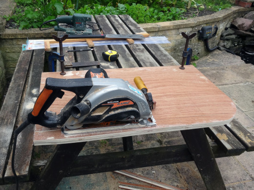 Using a circular saw to cut the wood panels to the correct width.