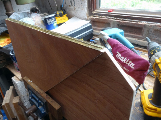 Clamping the two panels together, to join them with a piano; ensuring they open inwards e.g. the revers for the hinge on the hinge jamb.