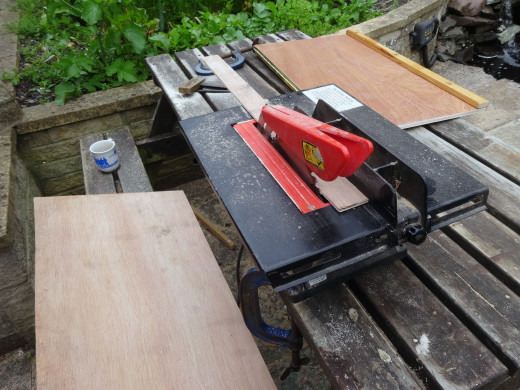 Cutting a strip from 4mm plywood to cover the middle piano hinge; fixing the cover to one panel only.