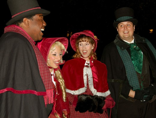 Four carolers dressed in traditional garb with seasonal colors sing Christmas songs.