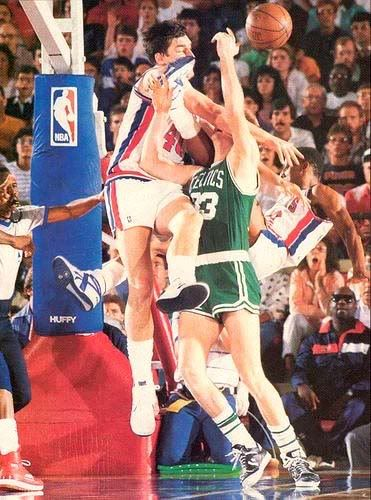 Bill Laimbeer (left) with a hard foul on Larry Bird (right).