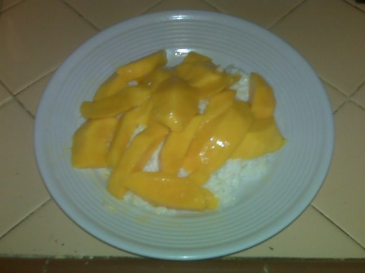 One mango, sliced, with coconut rice.