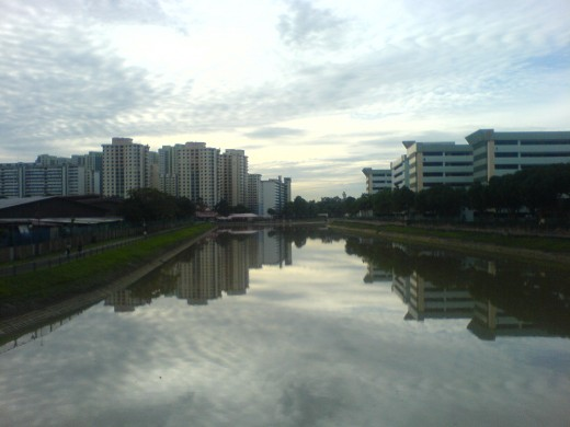 Calm Kallang River at dusk with housing blocks in the distance, Singapore