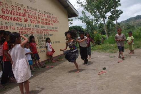 T`boli children enjoy a game called ``skipping rope`` using grass vines