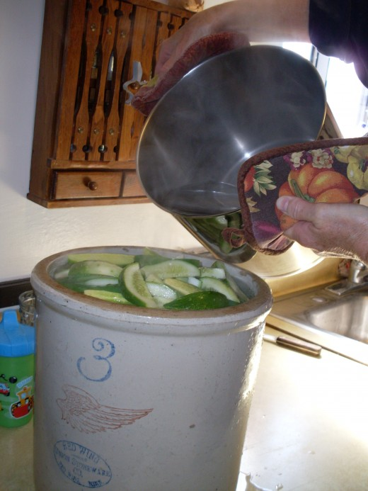 Pour boiling water over cucumber sticks to cover completely. This crock will soak enough pickle sticks for about seven quarts.