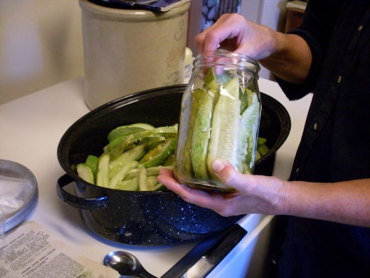 Meanwhile, pack cucumber sticks into clean jars. Pack tightly, but don't crush.
