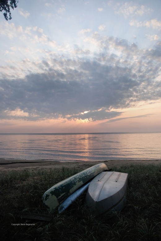 The sun eases into clouds shortly after rising on Lake Superior's Whitefish Bay near Paradise in Michigan's Upper Peninsula.