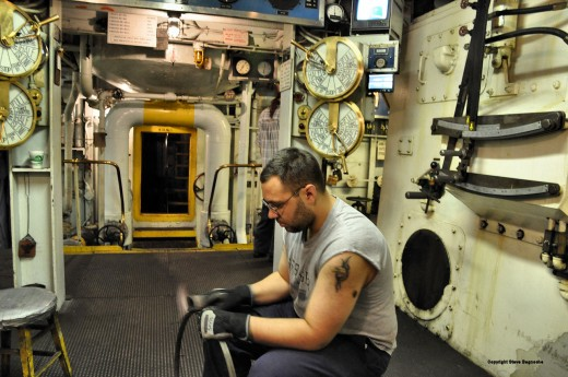 A crewmember cleans a piston ring in the Badger's engine room.