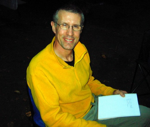 Me writing poetry by flashlight beside the campfire.