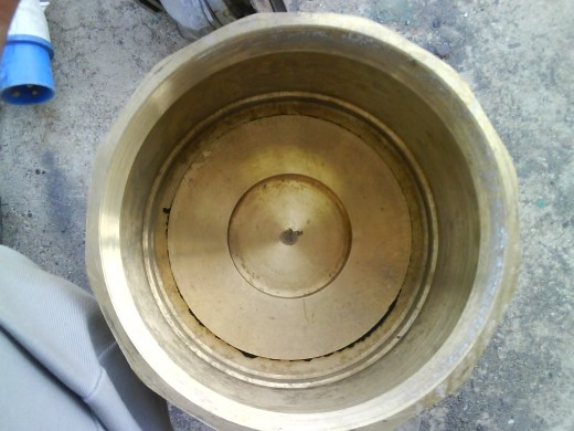 Inside view of foot valve: plate rests on the seat of valve due to force exerted by spring