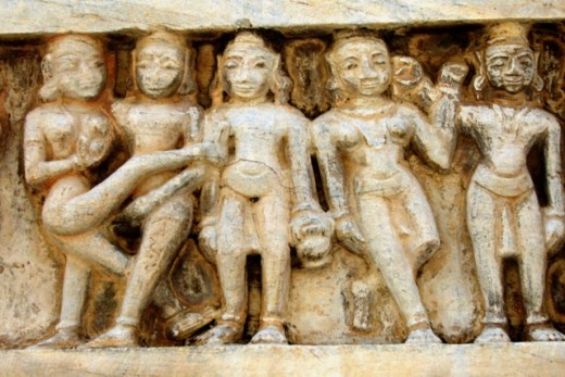 A hermit stands in the centre unperturbed  in company of a couple engaged in sex and two dancers in his right. Wall of Jagdishji's temple.