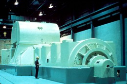 Steam Turbine Generator. The Steam enters from the large structure in the middle, turns a turbine (fan) which then turns the generator. The generator is the structure the man with the clipboard is standing in front of.