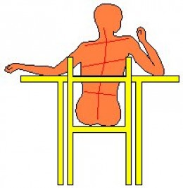 What happens to the spine when we sit on a chair?
