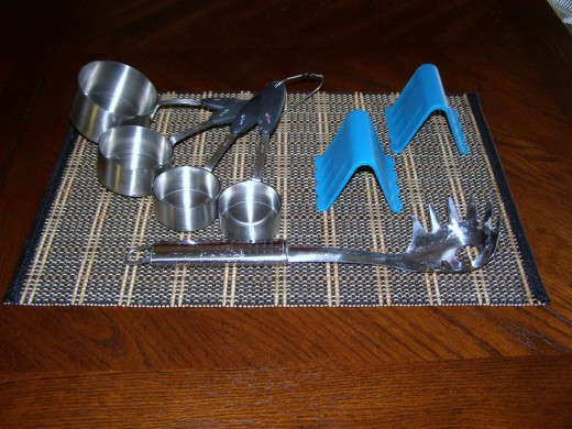 L clockwise; metal measuring cups, silicone, wedge pot holders, pasta server