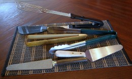 back; flip style tong,back centre from back; metal, rubber grip tong and wooden tong; foreground L to R; pie and cake server