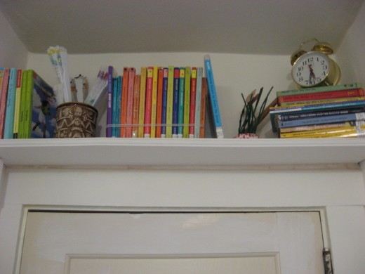 Look UP for possibilities for displaying books.  A shelf above a door utilizes otherwise unexploited space.