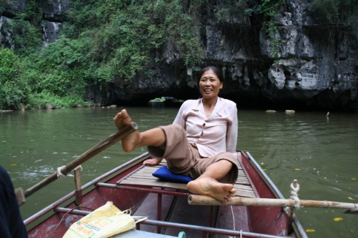 My helms woman rowing with her feet on the Tam Coc Cave Trip