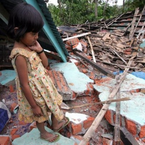 An Indonesian girl on her ruined house.