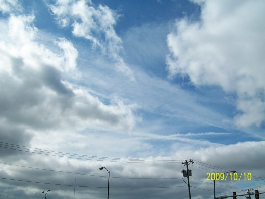 Looking at a greatly expanded chemtrail slanting through the center of the picture AND across the top of that one is another expansion. Also note the newer ones horizontally.  Wind was evidently strong at that altitude.