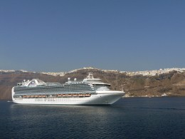 Norwegian Cruise Lines ship anchored beneath the clifftop town of Santorini, Greece.  Santorini is a popular destination for tours from Civitavecchia