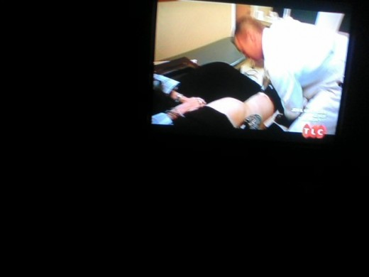 Mandy having her legs checked by the Doctor.
