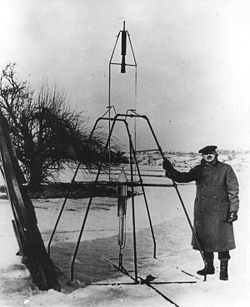 Robert Goddard and his liquid fueled rocket. Pictured are Goddard, the rocket, and a launching frame (large triangular structure at bottom). March 16, 1926. Photograph courtesy WikiCommons.