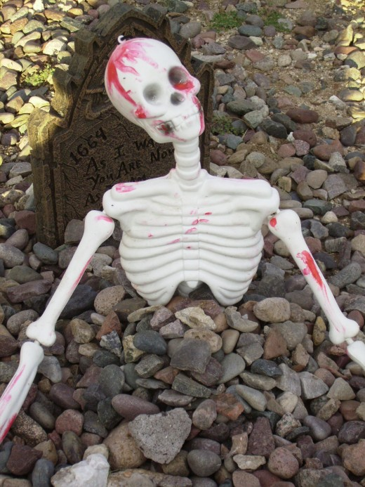 Skeleton rising from its grave on Halloween