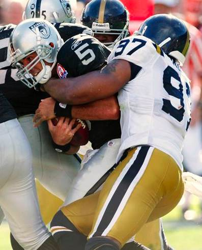 Oakland Raiders quarterback Bruce Gradkowski (5) is brought down by New York Jets linebacker Calvin Pace in the third quarter of an NFL football game in Oakland, Calif., Sunday, Oct. 25, 2009. (AP Photo/Ben Margot)