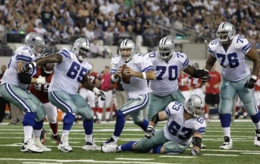 Dallas Cowboys quarterback Tony Romo (9) looks for an open receiver as he scrambles protected by his offensive line in the first half of an NFL football game against the Atlanta Falcons, Sunday, Oct. 25, 2009, in Arlington, Texas. (AP Photo/LM Otero)