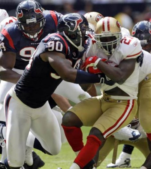 San Francisco 49ers running back Frank Gore (21) is tackled for a loss by Houston Texans defensive end Mario Williams (90) during the second quarter of a NFL football game Sunday, Oct. 25, 2009 in Houston. (AP Photo/David J. Phillip)