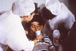 Cholera rehydration being administer by nurses to a patient with cholera (wikipedia)