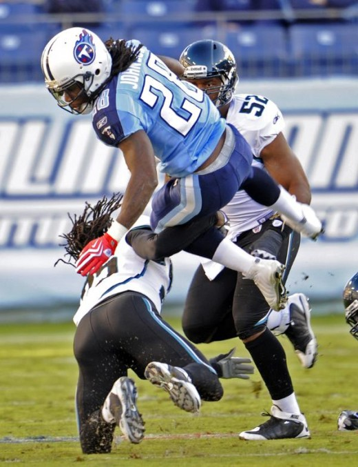 Tennessee Titans running back Chris Johnson (28) is tripped up by Jacksonville Jaguars safety Reggie Nelson, lower left, in the first quarter of an NFL football game in Nashville, Tenn., Sunday, Nov. 1, 2009. (AP Photo/John Russell)